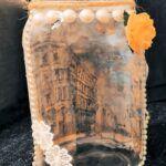 Lampion autorstwa Lilki. Na tylnej ściance ma przyklejony widoczek miasta zaś z przodu posiada perełki, u dołu białe kwiatki z koronki, a po prawej ma przyklejoną żółtą różyczkę.
