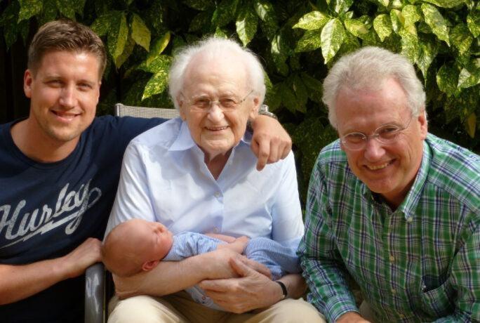 Po środku siedzi na krześle uśmiechnięty pradziadek i trzyma na rękach prawnuka. Po prawej jest dziadek, a po lewej ojciec. Wszyscy szczęśliwi.